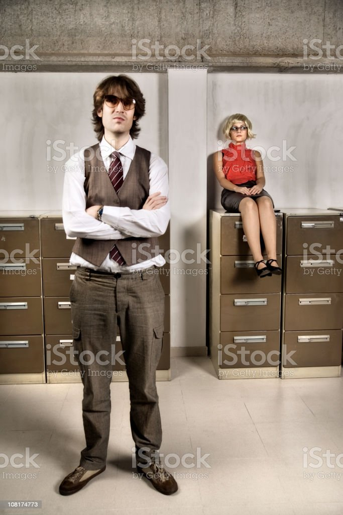 Young Woman Sitting on Filing Cabinet and Businessman Standing royalty-free stock photo