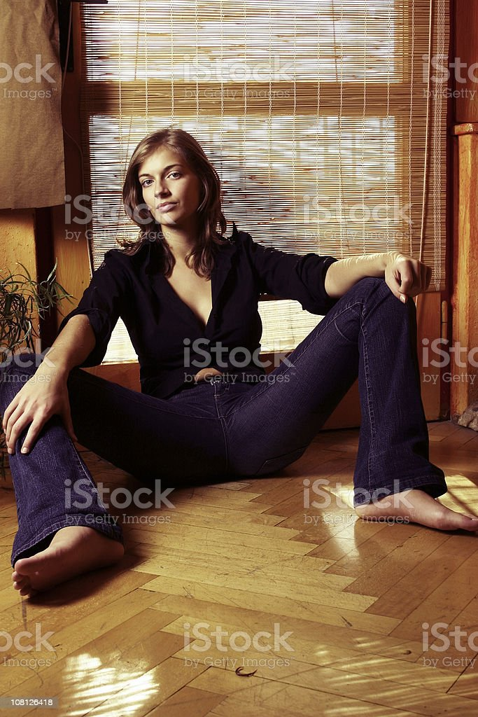 Young Woman Sitting on Floor of Home Near Door royalty-free stock photo