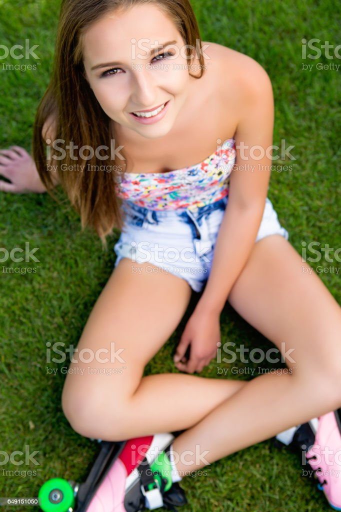 Young woman sitting on grass stock photo