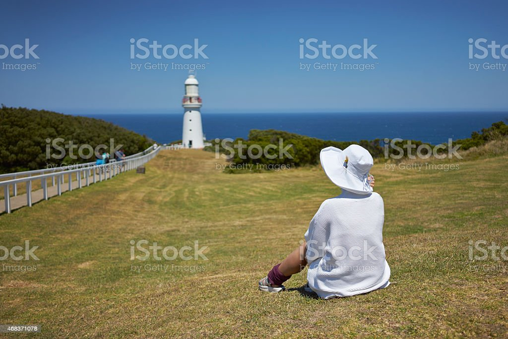 young woman sitting on grassland stock photo