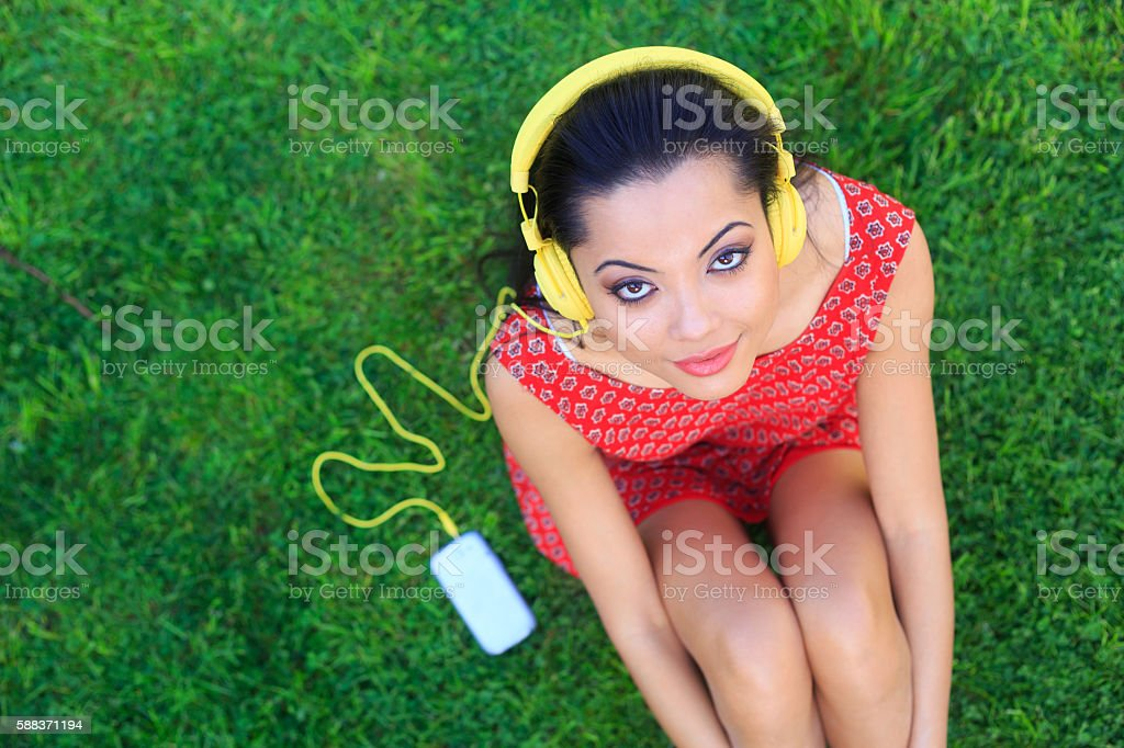 Young woman sitting on ground and listening music with headphones stock photo