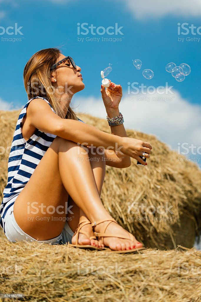 Young woman sitting on hay bales and blowing bubbles stock photo