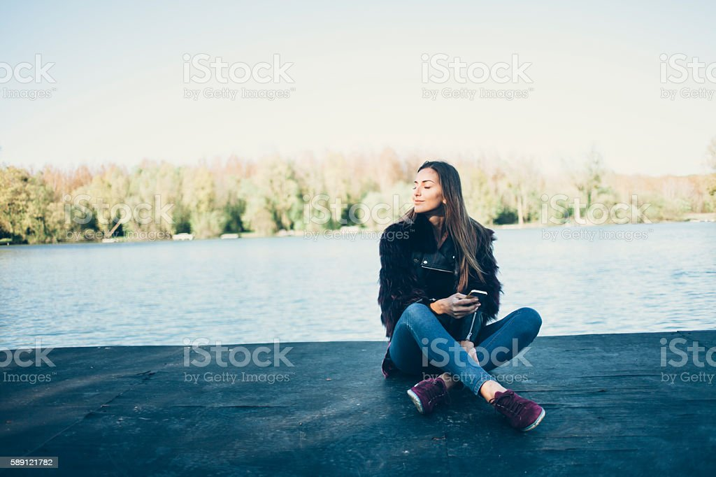 Young woman sitting on jetty and using smart phone stock photo
