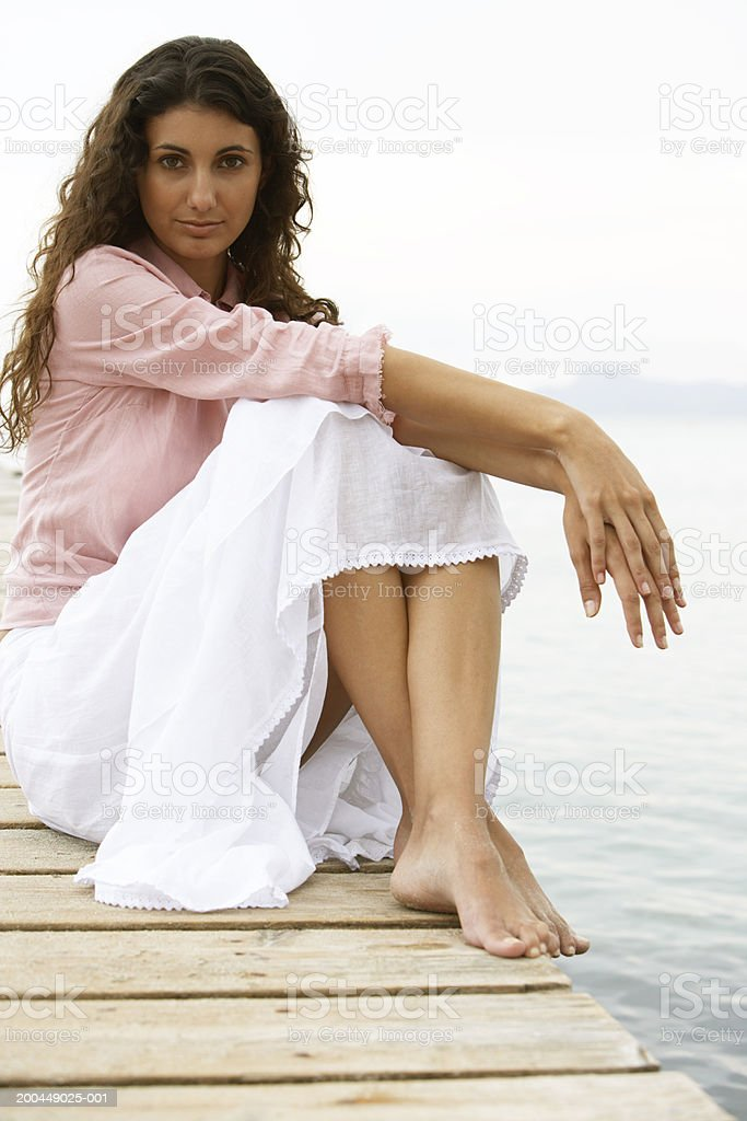 Young woman sitting on jetty, portrait royalty-free stock photo