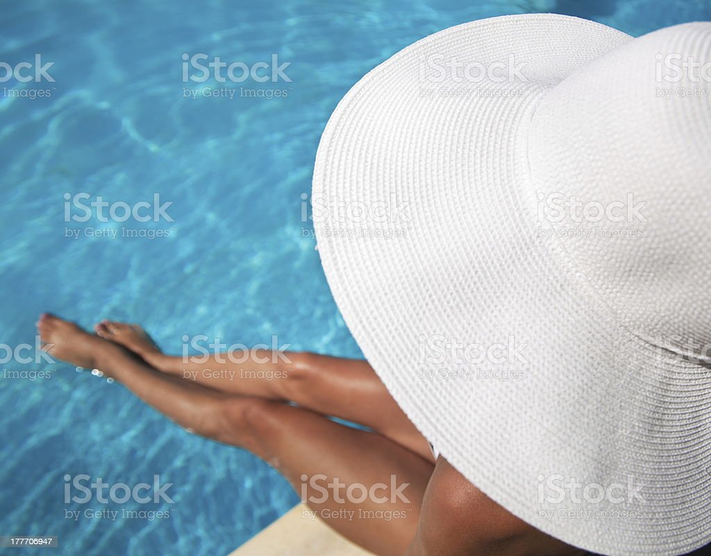 Young woman sitting on ledge of the pool. royalty-free stock photo