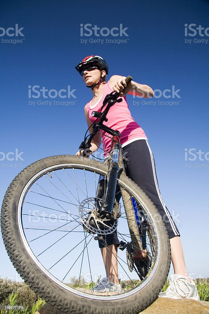 Young Woman Sitting on Mountain Bike Outside in Field royalty-free stock photo