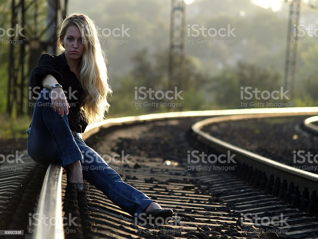 Young woman sitting on rail stock photo