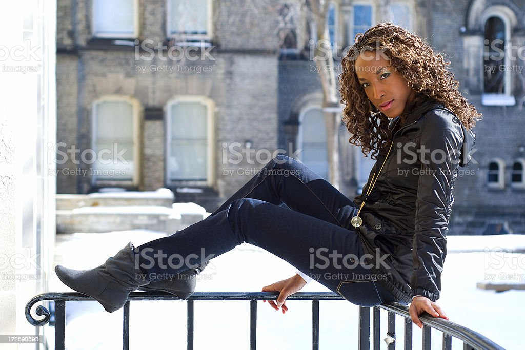 Young woman sitting on railing. royalty-free stock photo