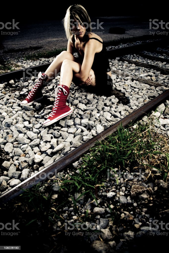 Young Woman Sitting on Railroad Tracks royalty-free stock photo
