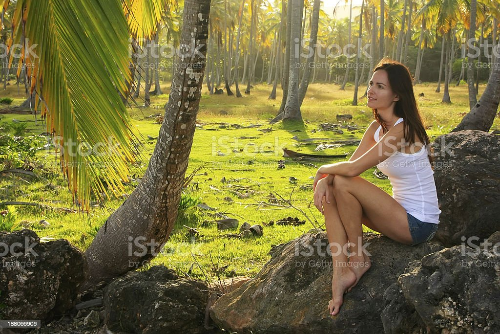 Young woman sitting on rocks in coconut trees grove stock photo