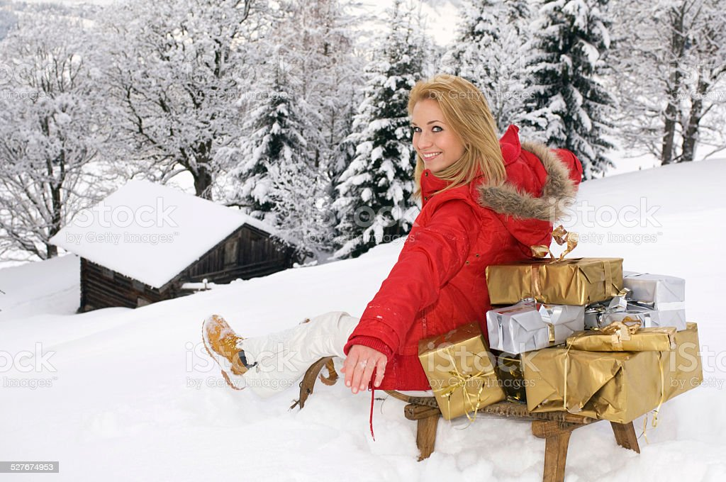 Young woman sitting on sledge with Christmas presents stock photo