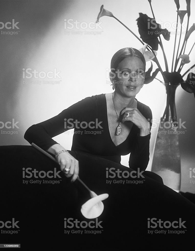 Young woman sitting on sofa and holding flower, portrait royalty-free stock photo