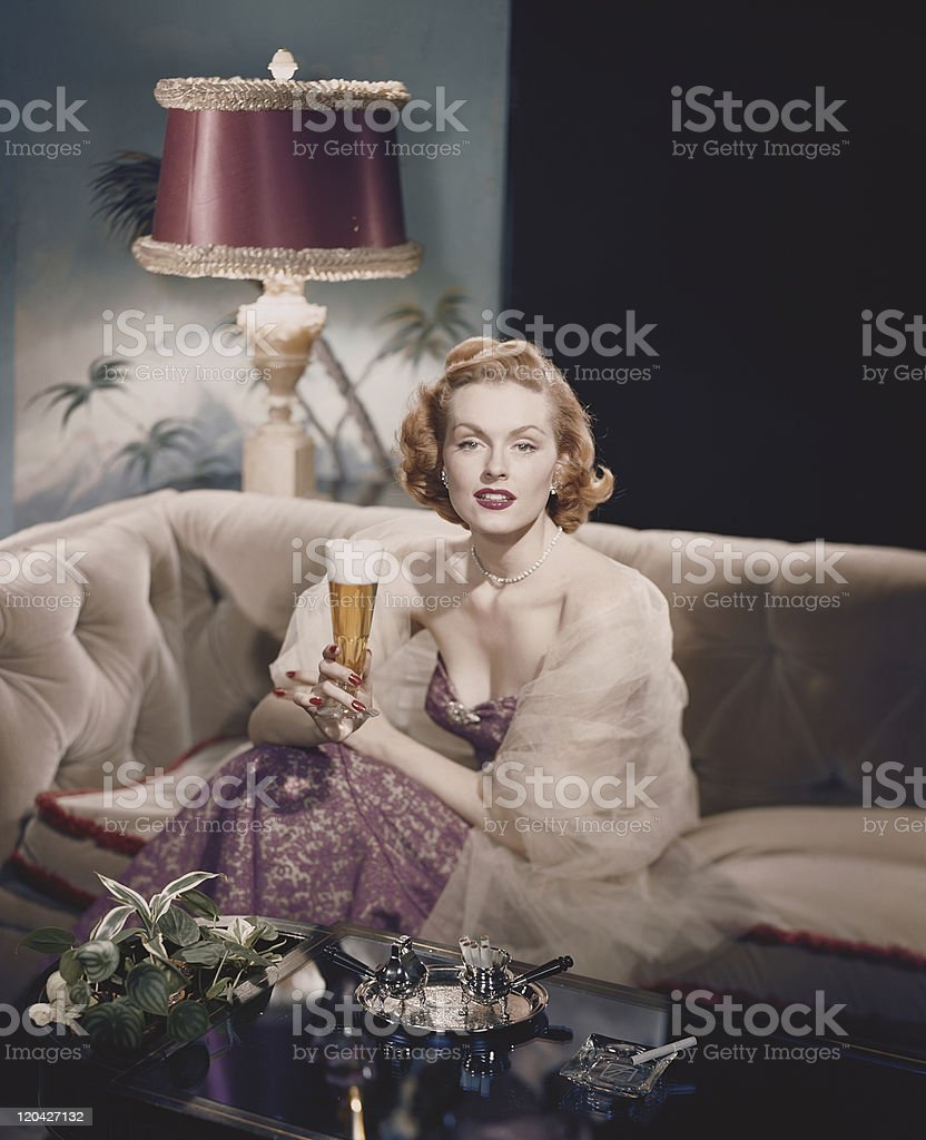 Young woman sitting on sofa holding beer glass, smiling, portrait stock photo