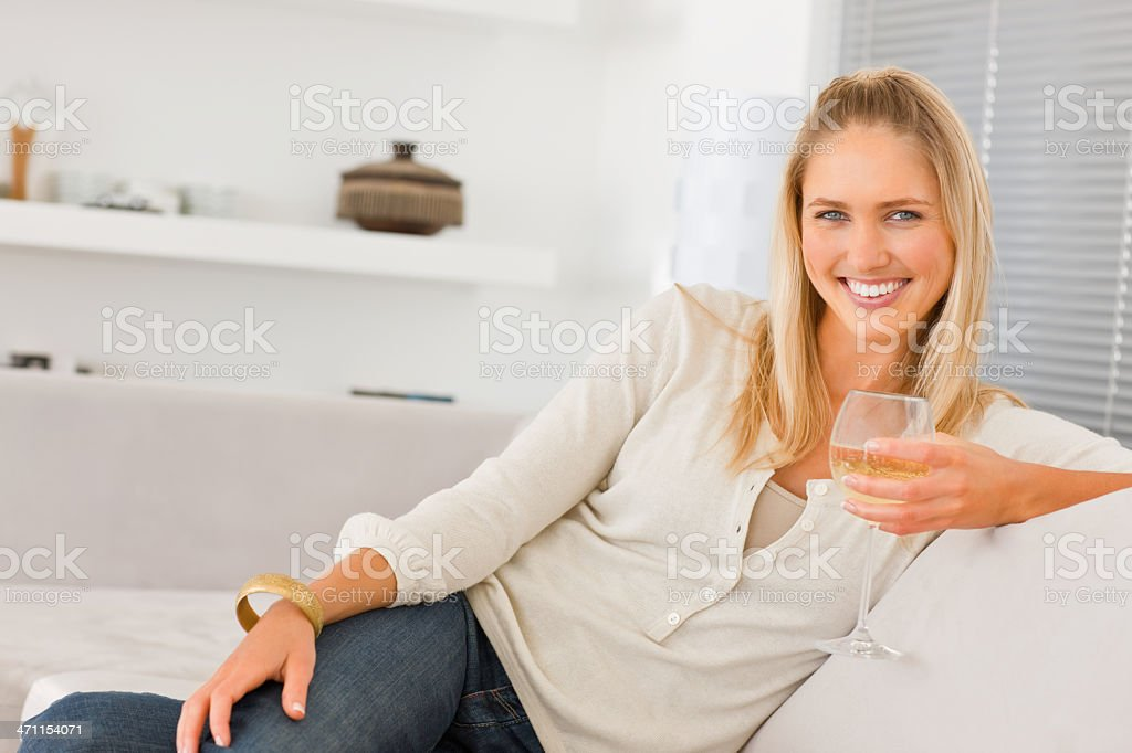 Young woman sitting on sofa holding glass royalty-free stock photo