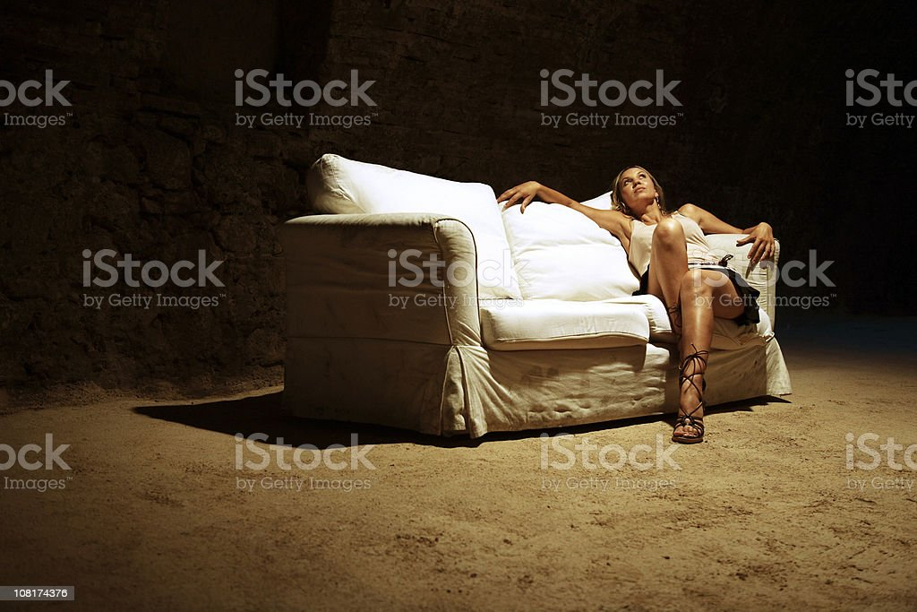 Young Woman Sitting on Sofa in Abandoned Area royalty-free stock photo