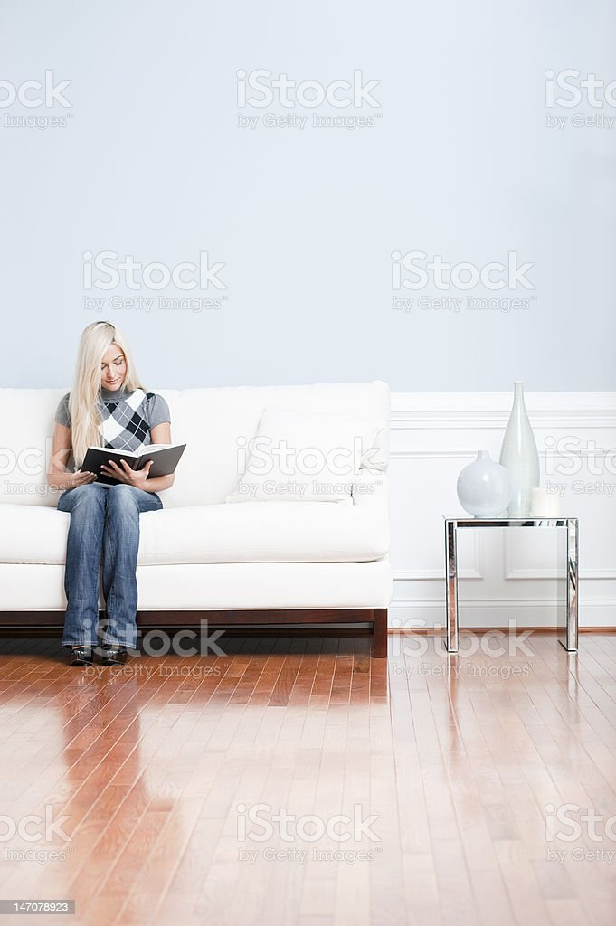 Young Woman Sitting on Sofa Reading Book royalty-free stock photo