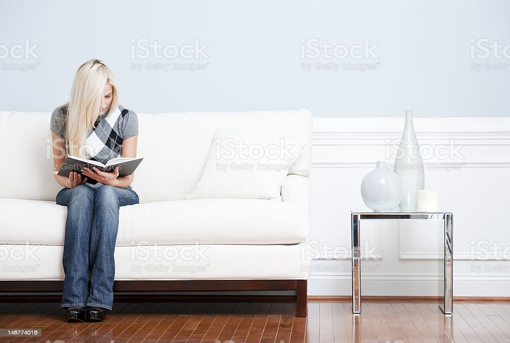 Young Woman Sitting on Sofa Reading royalty-free stock photo