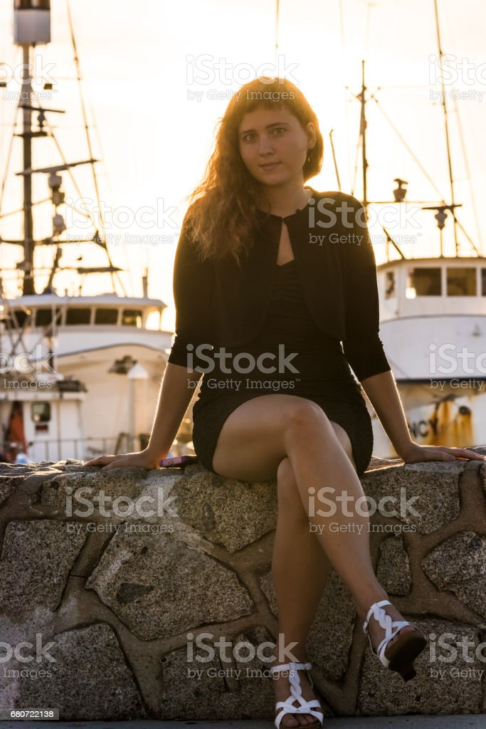 Young woman sitting on stone fence in harbor in San Diego, California during sunset stock photo