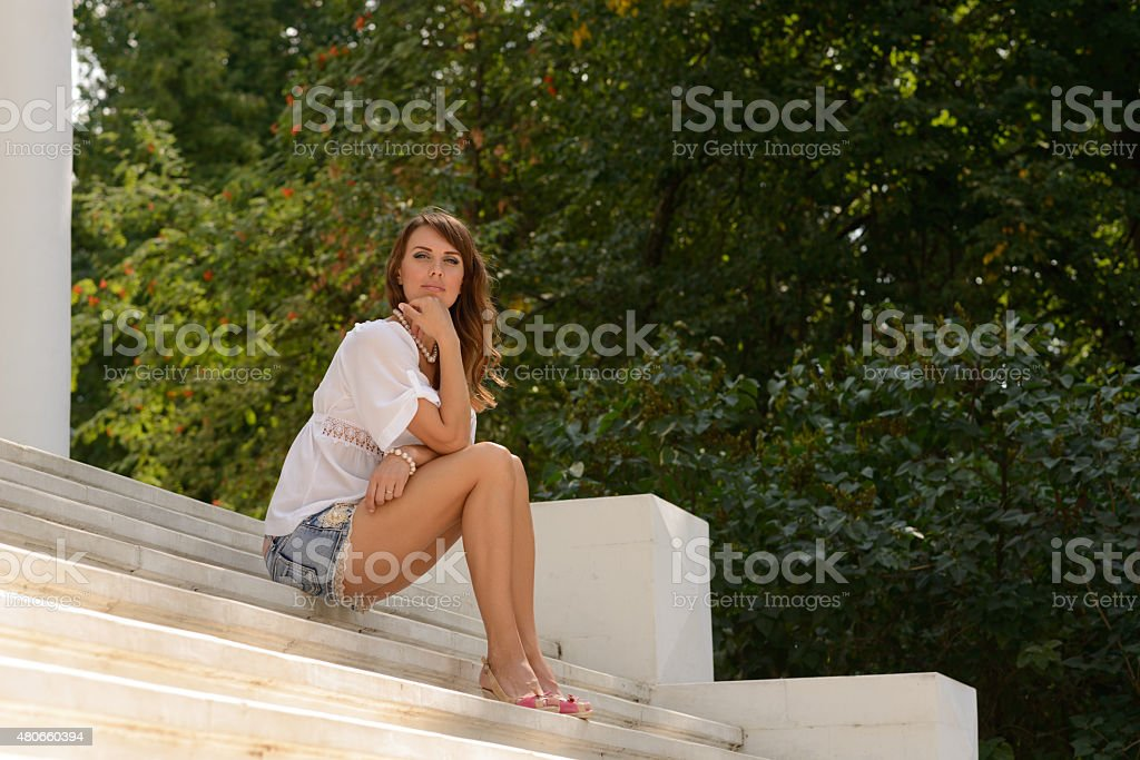 young woman sitting on stone stairs and looking at camera stock photo