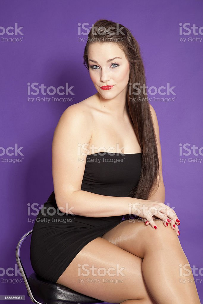 Young woman sitting on stool stock photo