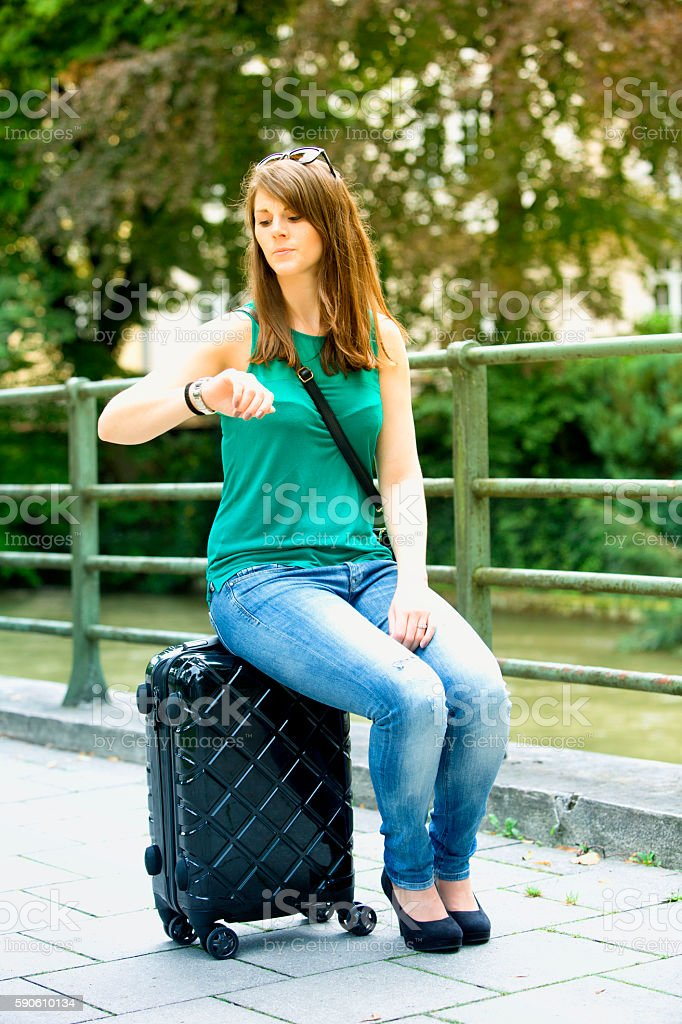 young woman sitting on suitcase and looking at watch stock photo