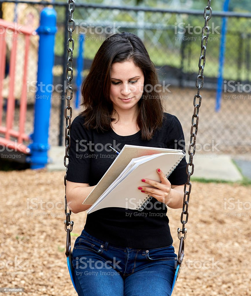 Young Woman sitting on Swing while Sketching on Notebook stock photo