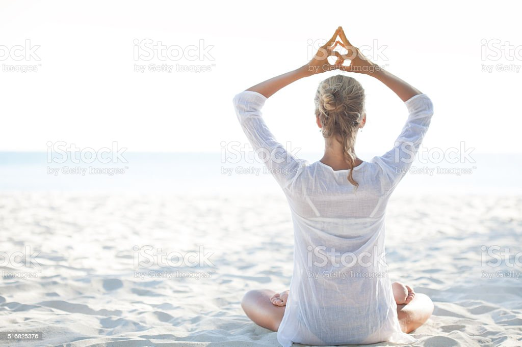 Young woman sitting on the  beach and meditating stock photo