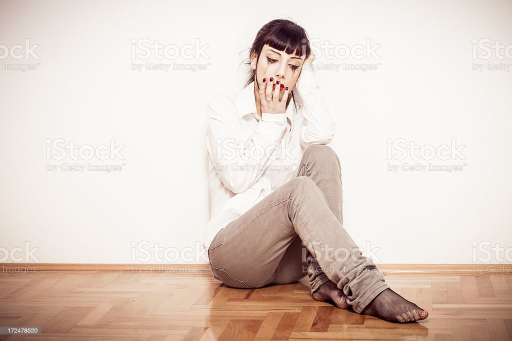 Young woman sitting on the floor and crying stock photo