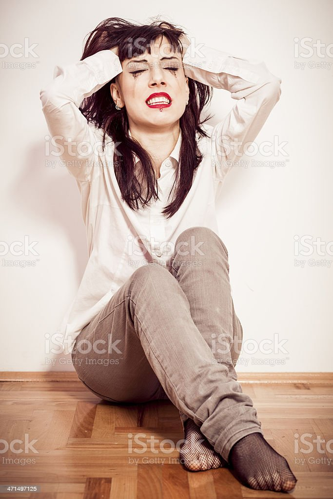 Young woman sitting on the floor and crying royalty-free stock photo