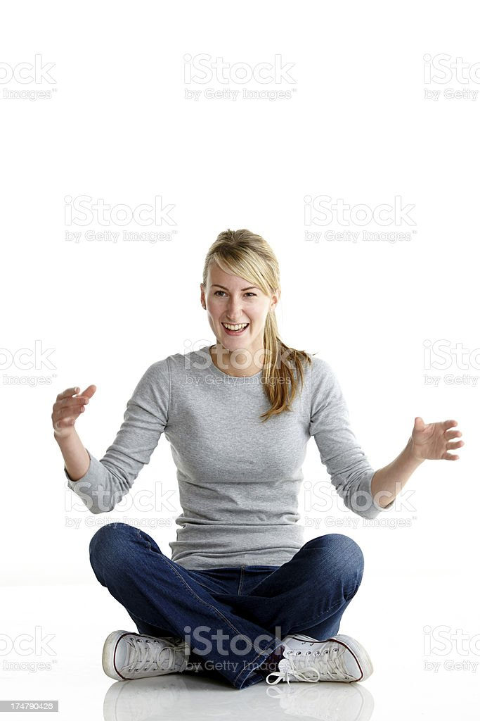 Young woman sitting on the floor laughing royalty-free stock photo