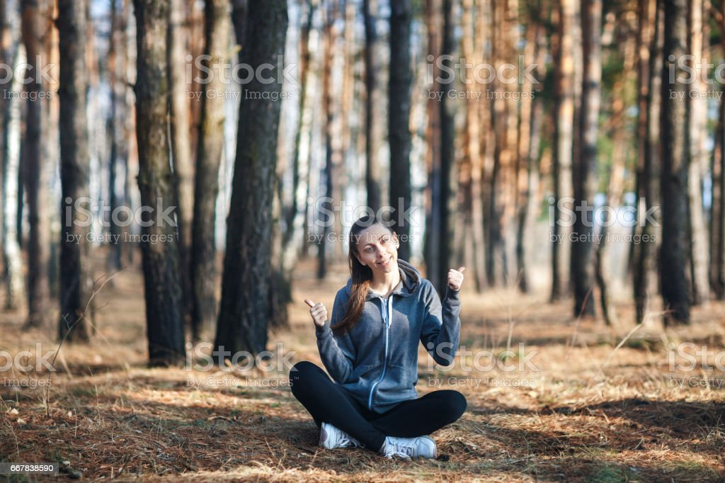 Young woman sitting on the grass in the forest on sunny day, shows thumb up stock photo