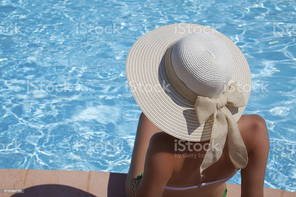Young woman sitting on the ledge of the pool stock photo