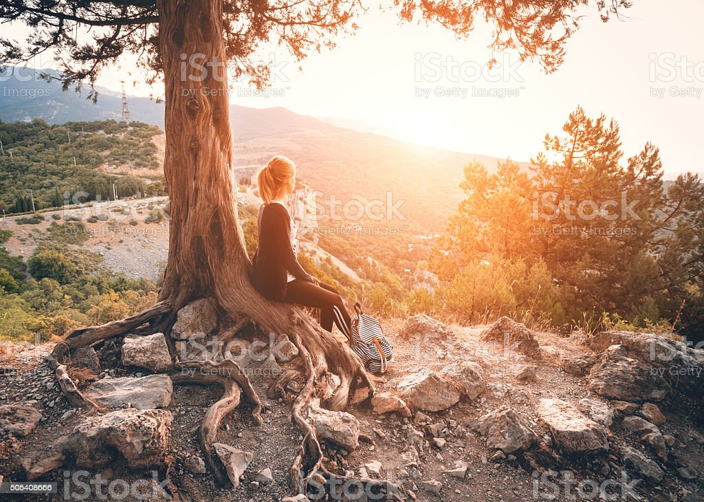 Young woman sitting on the mountain at sunset. Summer landscape stock photo