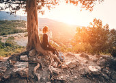 Young woman sitting on the mountain at sunset. Summer landscape