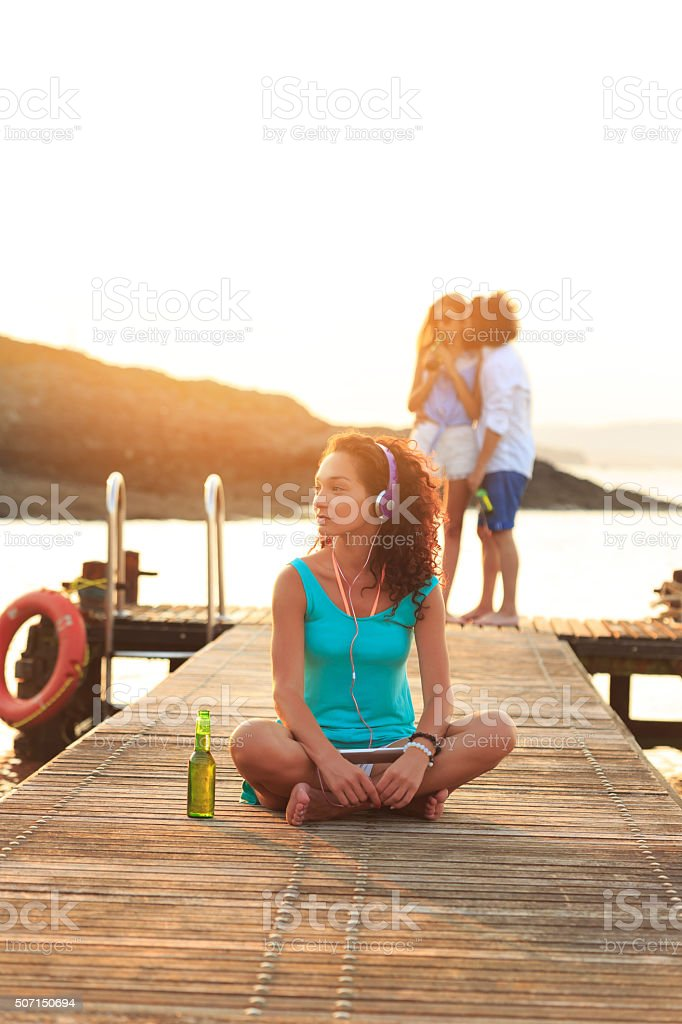 Young woman sitting on the pier listening music stock photo