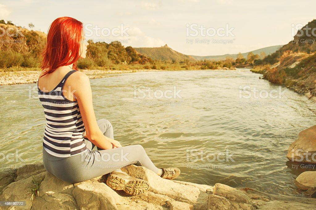 Young woman sitting on the river bank. stock photo