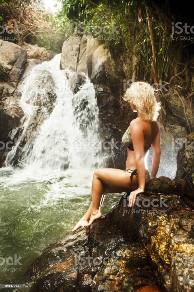 Young woman sitting on the rock next to waterfall. stock photo