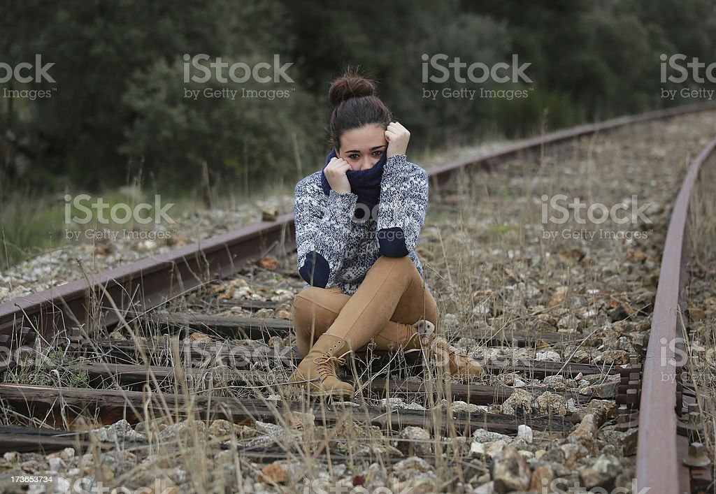 Young woman sitting on the train tracks royalty-free stock photo