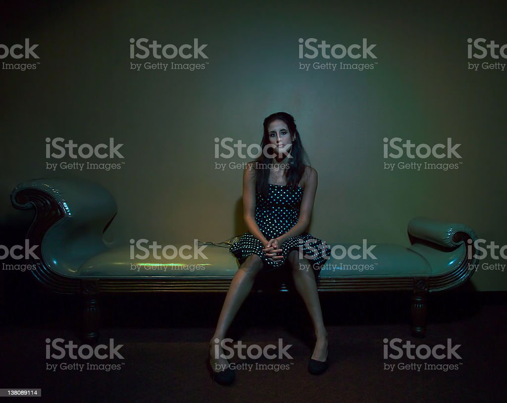 Young Woman Sitting on Vinyl Chaise, Low Key royalty-free stock photo