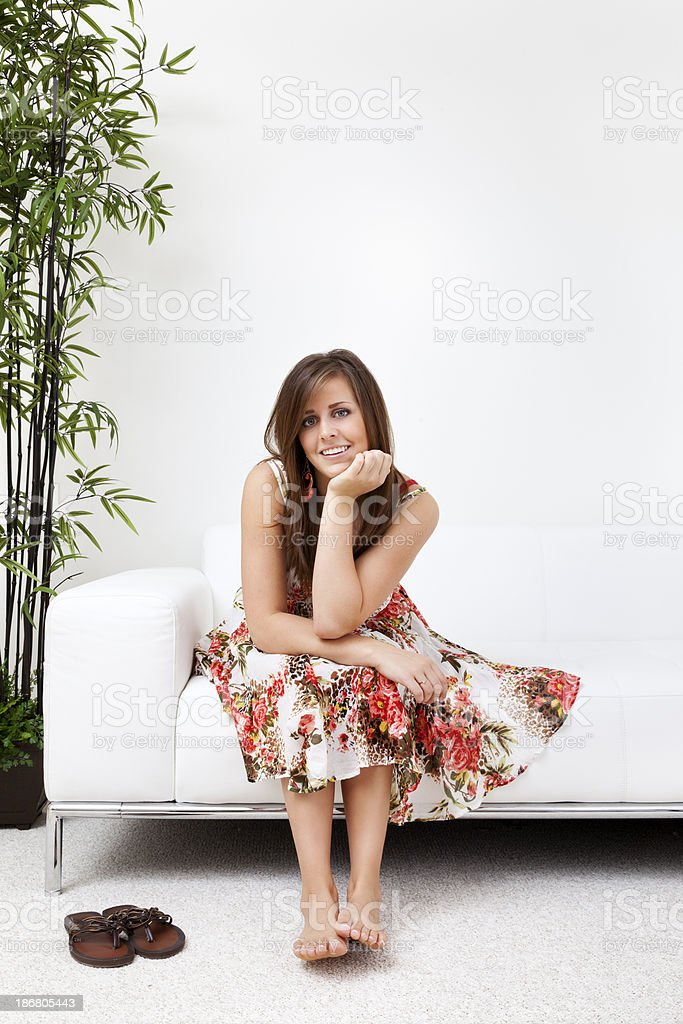 Young Woman Sitting on White Leather Sofa stock photo