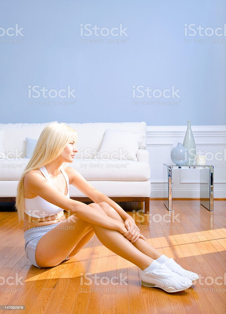 Young Woman Sitting on Wood Floor royalty-free stock photo