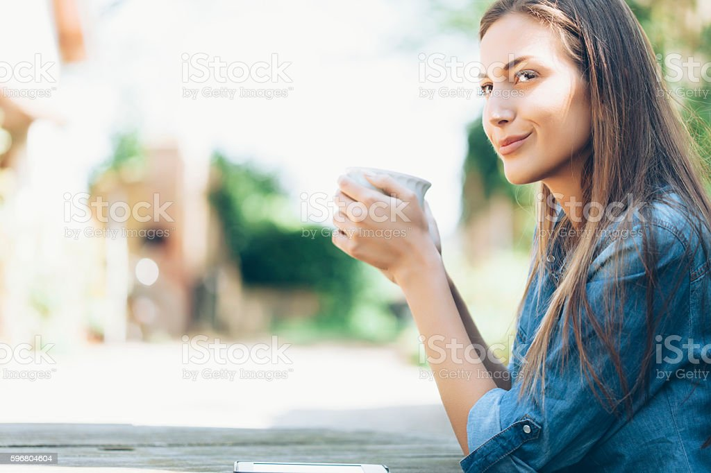 Young woman sitting outdoors and drinking coffee stock photo