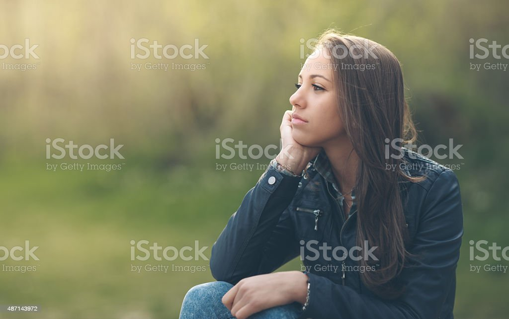 Young woman sitting outdoors stock photo