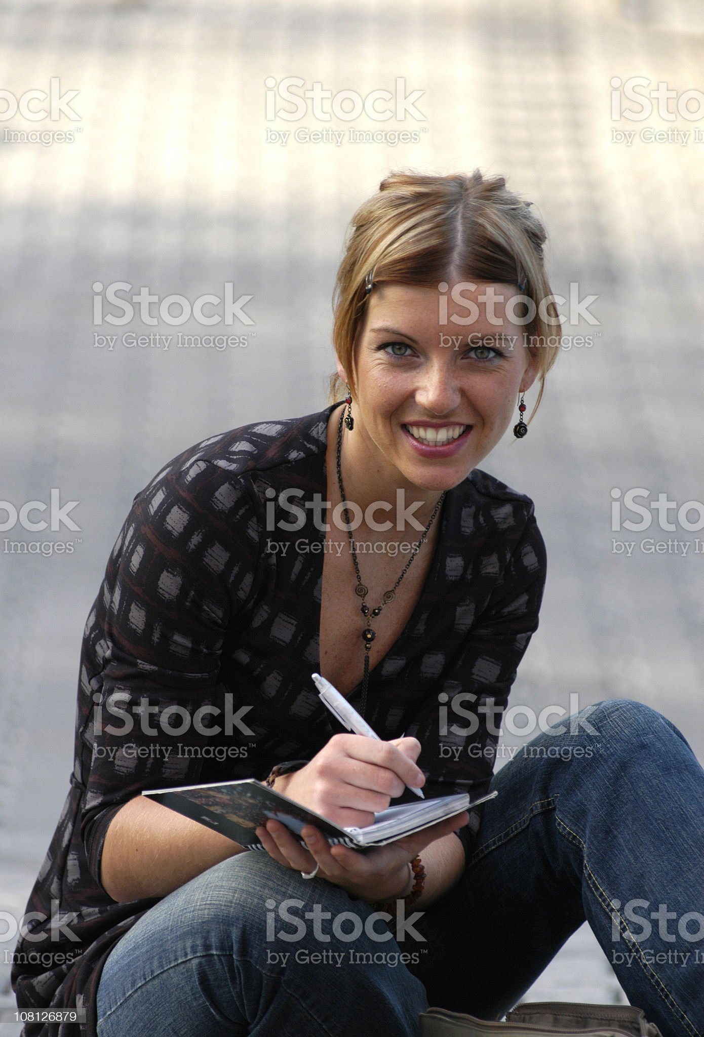 Young Woman Sitting Outside and Writing in Book royalty-free stock photo