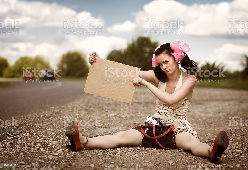 Young Woman Sitting Roadside Holding Blank Sign royalty-free stock photo