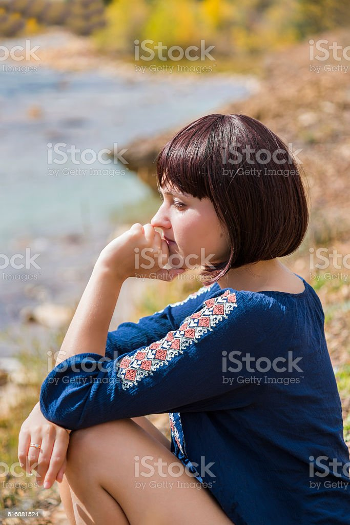 Young woman sitting thinking by light blue creek stock photo