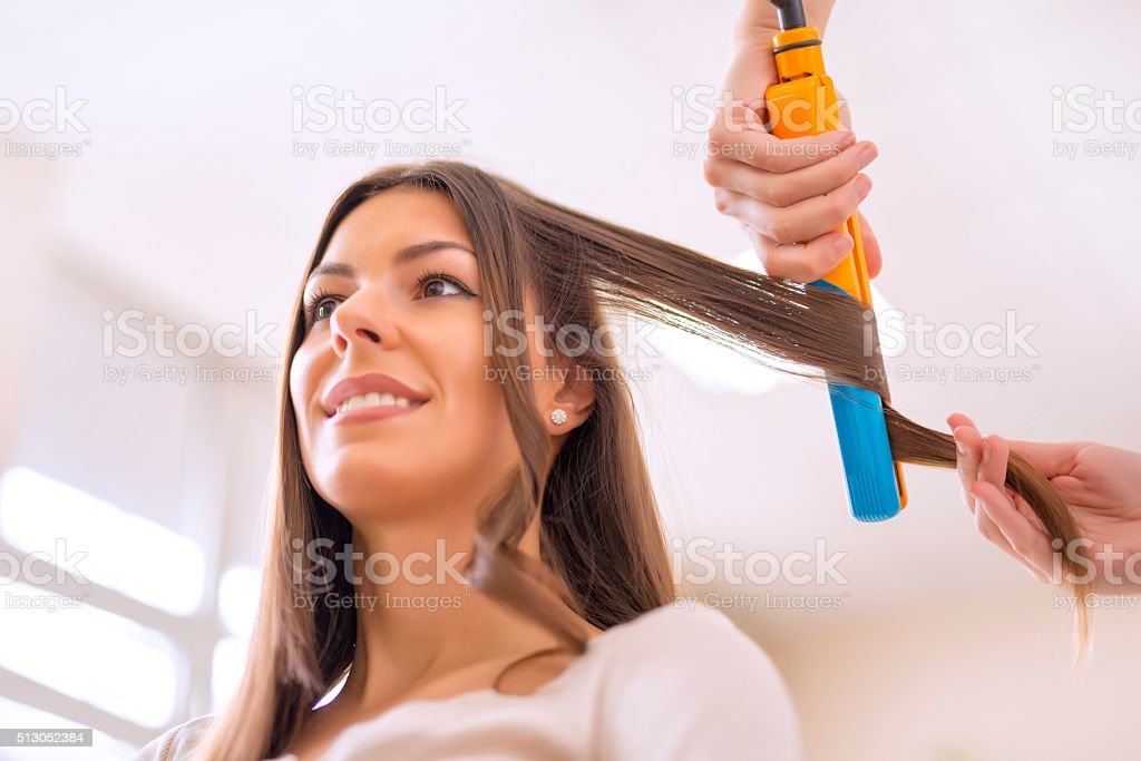 Young woman sitting while the hairdresser is styling her hair stock photo