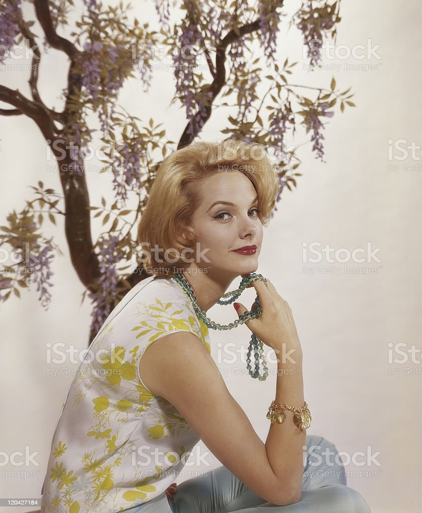 Young woman sitting with tree in background, smiling, portrait stock photo