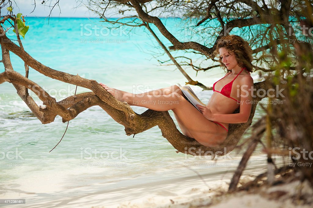 Young woman sittinig on tropical beach and reading book royalty-free stock photo