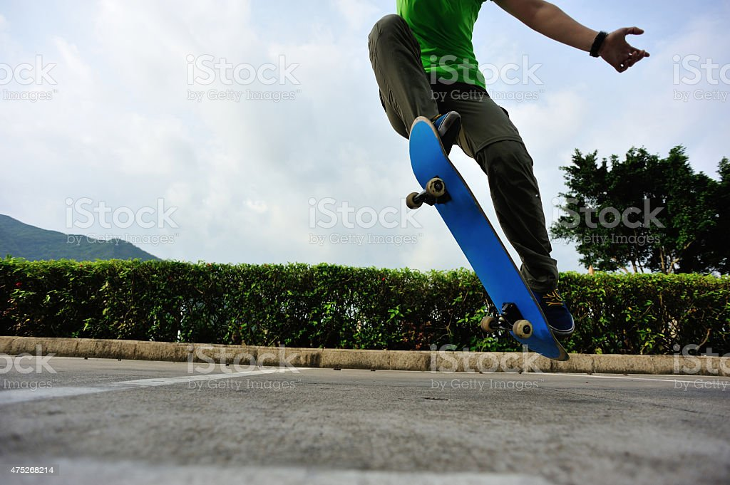 young woman skateboarder doing ollie trick at parking lot stock photo